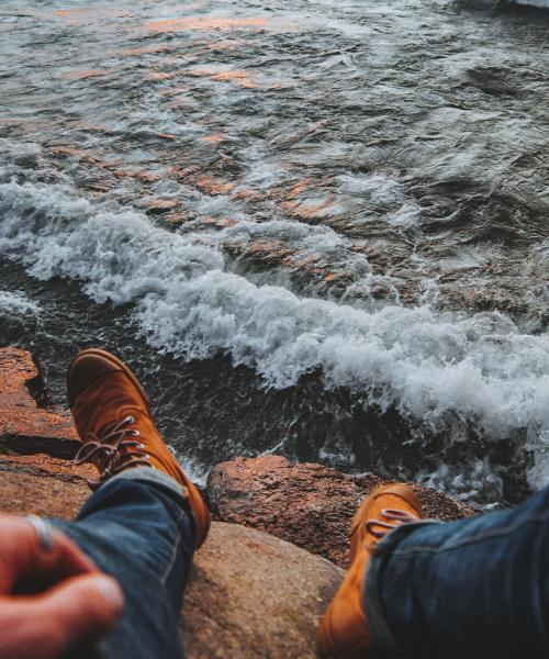 Student's feet in front of Lake Superior