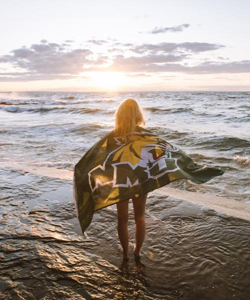 Female student standing in Lake Superior with NMU flag