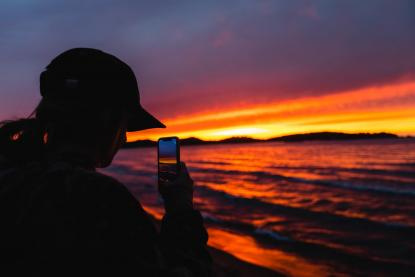 Student taking a photo of a Lake Superior sunset