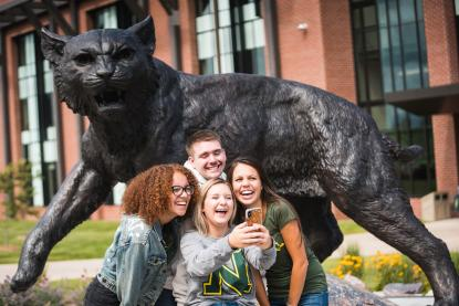 Four students taking a selfie in front of NMU's Wildcat Statue