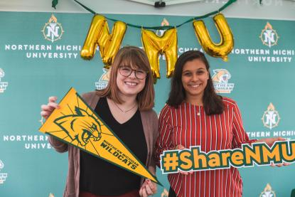 Two female students in an NMU photo booth