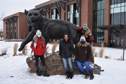 Middle College students with Wildcat statue
