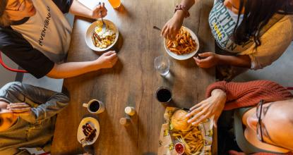 Overhead photo of students eating at a dining table