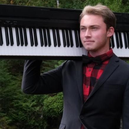 man in flannel and suit jacket holding a keyboard on his shoulder in the woods