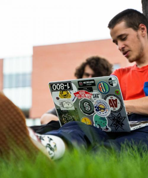 Male student on laptop sitting on ground by a tree