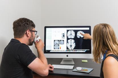 Student and faculty member doing brain research on a computer