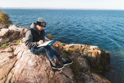 Male student writing in a journal next to Lake Superior