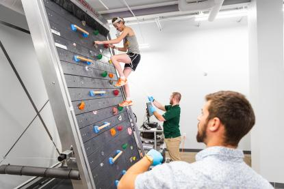 Male student climbing indoor rock wall treadmill