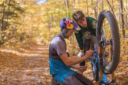 Students working on a mountain bike in the woods