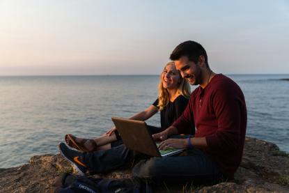 Male and female student on a laptop near Lake Superior
