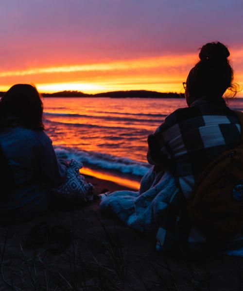 Two students watching a sunset over Lake Superior