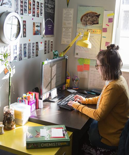 Female student working at desk in residence hall room