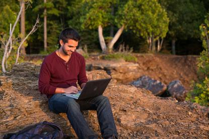 Male student on laptop in nature