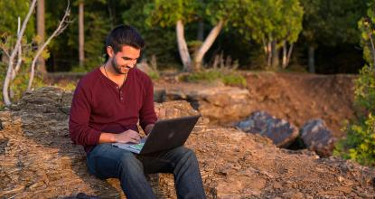 Male student on laptop by Lake Superior