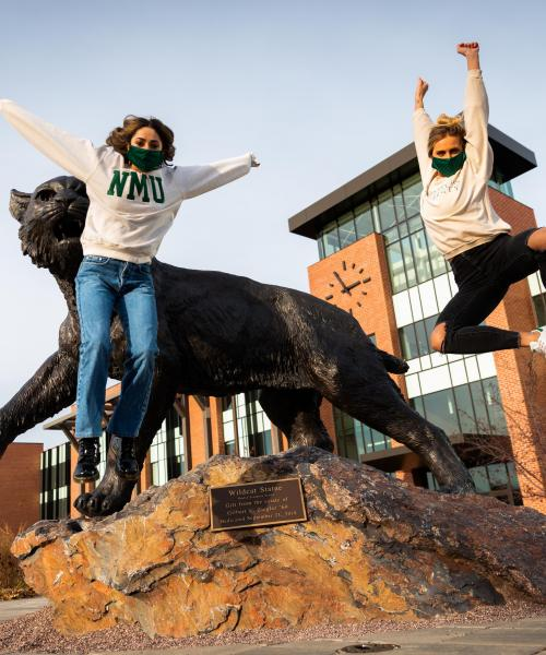 Students jumping in front of Wildcat statue