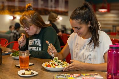 Two female students eating at Northern Lights Dining