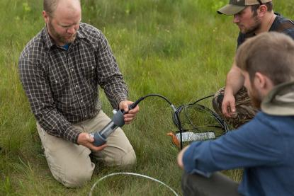 Male faculty member doing soils research with two male students