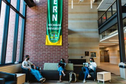 Three students sitting 6 feet apart while inside on campus