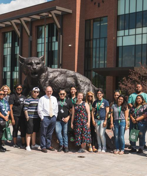 Aim North students with President Erickson at Wildcat statue