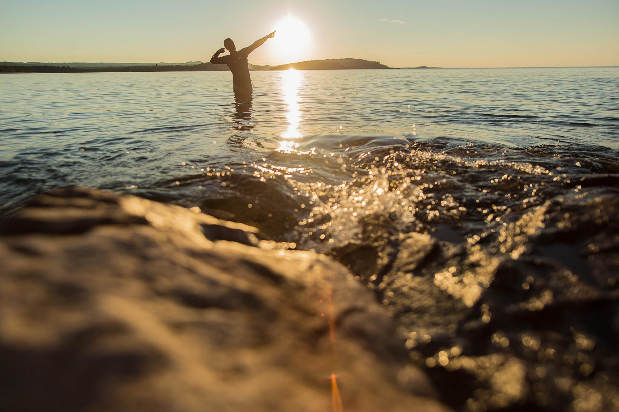 Silhouette of student standing in Lake Superior at sunset