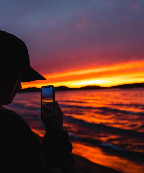 Student taking photo of a sunset over Lake Superior