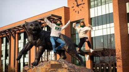 students jumping in front of the wildcat statue